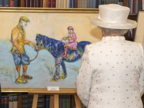Britain's Queen Elizabeth looks at a painting presented to her during a visit to Germany's President's official residence, in Berlin