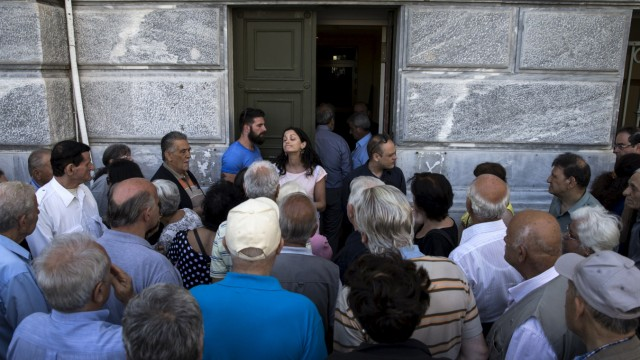 People, most of them pensioners, argue with a staff member outside a closed National Bank branch at the bank's headquarters in Athens