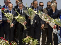 Ministers hold bouquets of flowers as they pay their respects in front of a makeshift memorial at the beachside of the Imperial Marhaba resort, which was attacked by a gunman in Sousse