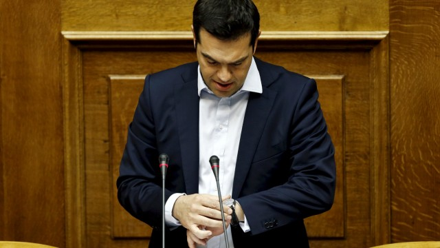 File photo of Greek PM Tsipras looking at his watch as he delivers a speech during a parliamentary session in Athens