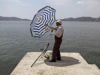 Fisherman adjusts a sun umbrella in the town of Elefsina