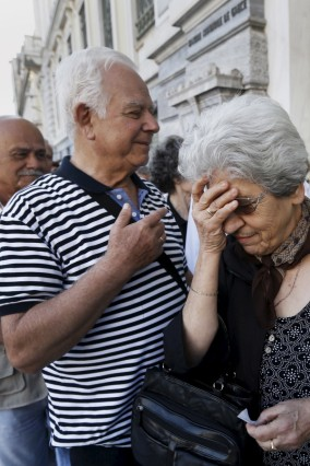 A pensioner reacts after receiving a priority ticket to receive part of their pensions outside a bank in Athens