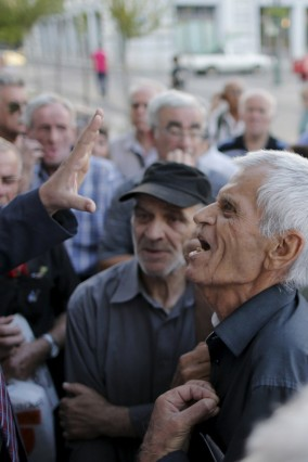 A pensioner argues with an official as they scuffle to enter a National Bank branch to receive part of their pensions in Athens
