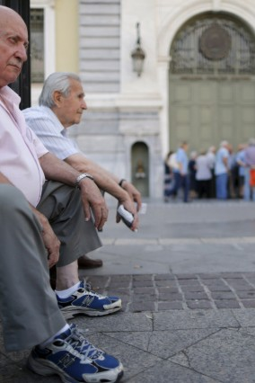 Pensioners sit outside a National Bank branch as they wait to receive part of their pension in Athens