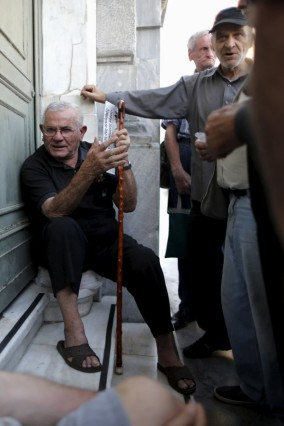 Pensioners wait outside a National Bank branch to receive part of their pension in Athens