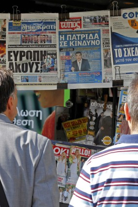 People look at newspapers showing the results of yesterday's referendum in central Athens