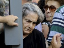 A pensioner exits a National Bank branch after receiving part of her pension at the city of Iraklio in the island of Crete