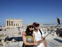 Ein Touristen-Paar macht ein Selfie-Foto vor der Akropolis in Athen