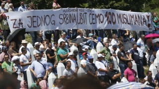 A banner reading 'For one Serbian we are going to kill 100 muslims!', a quote attributed to Serbian PM Vucic, is seen during a reburial ceremony in Potocari, near Srebrenica
