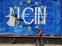 A man walks past graffiti in Athens, Greece