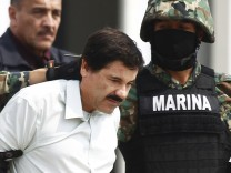 File photo of Joaquin 'Shorty' Guzman being escorted by soldiers during a presentation at the Navy's airstrip in Mexico City