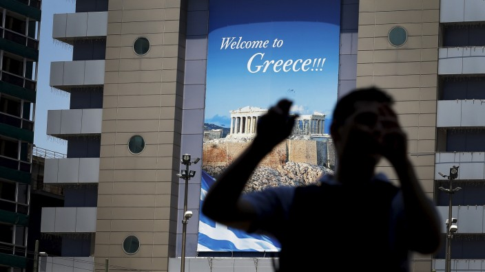 A man walks past a tourism poster in Athens, Greece