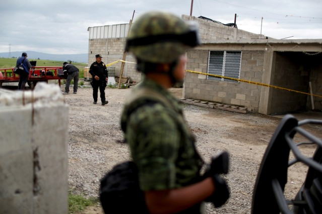 Soldier and policemen keep watch outside a warehouse where a tunnel, connected to the Altiplano Federal Penitentiary and used by drug lord Joaquin 'El Chapo' Guzman to escape, was located in Almoloya de Juarez
