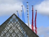 Alphajets from the French Air Force Patrouille de France fly over the Pyramid of the Louvre Museum during the traditional Bastille day military parade in Paris