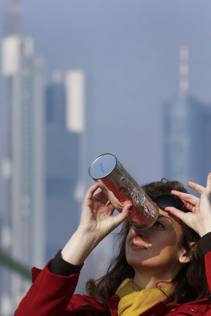 Simic uses a self-made monocular to watch a partial solar eclipse on the bank of river Main in front of the skyline of Frankfurt