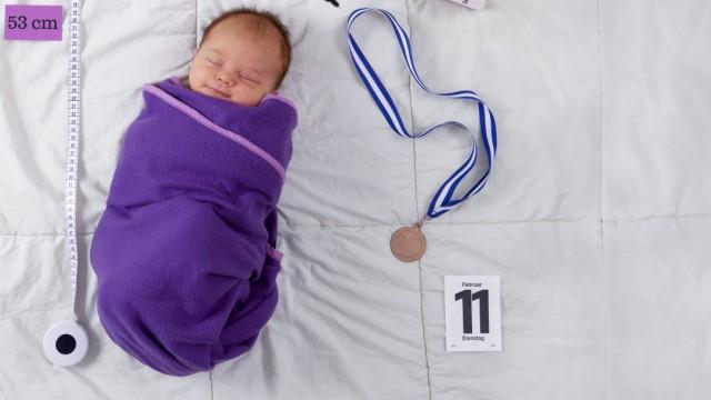 Baby liegt neben kreativ zusammengestellten Utensilien mit Daten zur Geburt, Baby is lying next to creative utensils