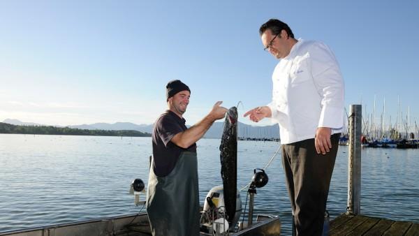 Chiemseefischer Florian Kirchmeier übergibt einen Waller an Rüdiger Linke