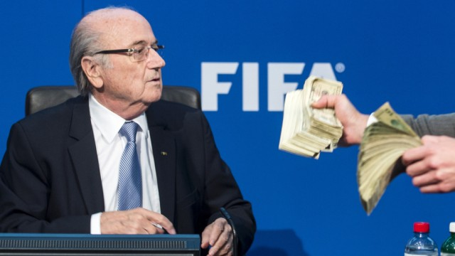 Der britische Comedian Simon Brodkin tritt während einer Pressekonferenz mit nachgemachten Dollar-Scheinen an Fifa-Präsident Sepp Blatter heran.