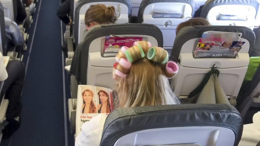 Reisende Frau mit Lockenwicklern Touristen und Passagiere am Internationalen Flughafen Muenchen im