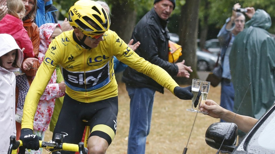 Team Sky rider Chris Froome of Britain, the race overall leader's yellow jersey, drinks a glass of champagne as he cycles during the final 21st stage of the Tour de France cycling race