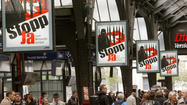 People walk under posters of the Swiss People's Party at the central station in Zurich