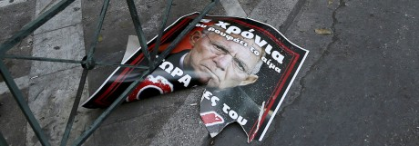 A torn referendum campaign poster depicting German Finance Minister Schaeuble is seen on a street in Athens