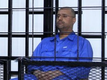 Saif al-Islam Gaddafi, son of late Libyan leader Muammar Gaddafi, attends a hearing behind bars in a courtroom in Zintan