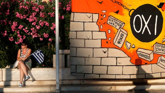 A woman sits near a mural depicting a wrecking ball smashing a wall of austerity measures in Athens