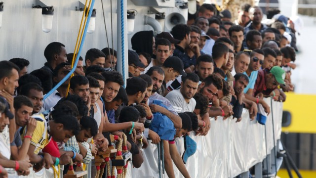 Migrants wait to disembark from the Irish Navy ship LE Niamh in the Sicilian harbour of Messina
