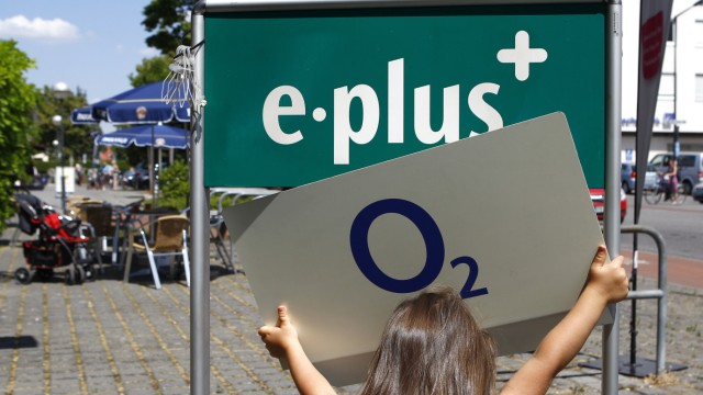 Girl holds up logo of O2 Deutschland German daughter of Spain's Telefonica close to E-Plus logo in front of E-Plus store in Germering