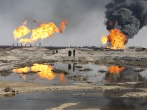Excess gas is burned off near workers at the Rumala oil field