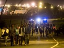 Flüchtlinge versuchen von Calais aus den Eurotunnel zu erreichen