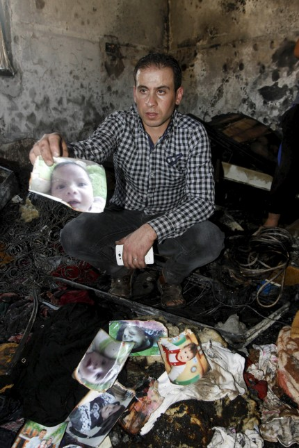 Relative of 18-month-old Palestinian baby Ali Dawabsheh, who was killed after his family's house was set to fire in a suspected attack by Jewish extremists, shows his picture at the burnt house in Duma village near the West Bank city of Nablus