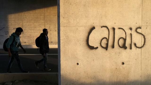 Migrants walk near a wall that is marked with the word 'Calais' as they advance towards the Channel Tunnel access near Calais