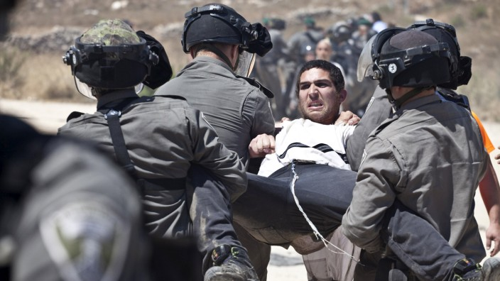 Israeli paramilitary police detain a Jewish settler protesting the demolition of two partially-built dwellings in the West Bank Jewish settlement of Beit El near Ramallah