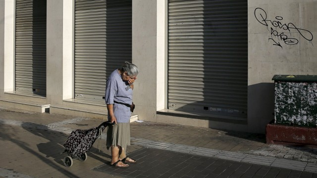 A woman pulling a shopping cart reacts outside a closed Eurobank branch in Athens