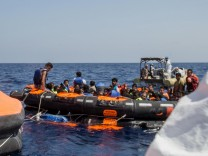 Surviving migrants are brought aboard Irish and Italian Navy life-boats in the area where their wooden boat capsized and sank off the coast of Libya