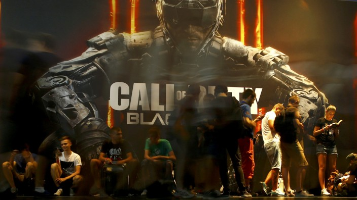 Visitors queue to play the video game 'Call Of Duty: Black Ops III' during the Gamescom fair in Cologne