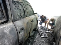 Men take photos of OSCE car which was burnt overnight near its office in Donetsk