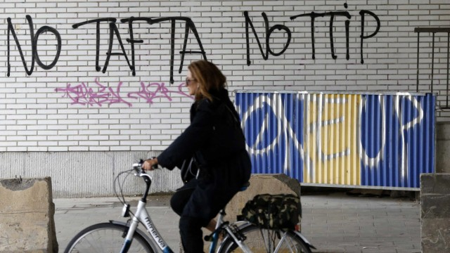 Cyclist rides past graffiti that reads, 'No TAFTA, No TTIP', in Brussels, Belgium