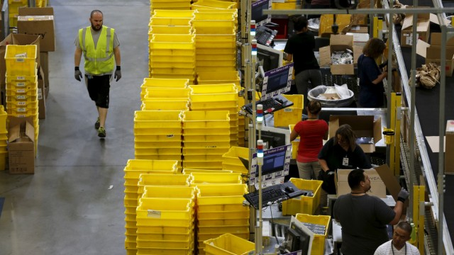 Workers sort arriving products at an Amazon Fulfilment Center in Tracy