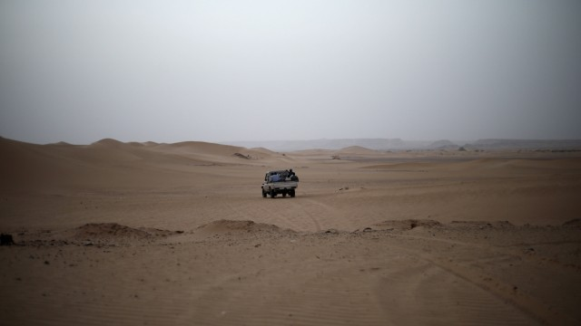 A vehicle transporting a group of African migrants drives through the desert on their journey from Ghat in southwest Libya