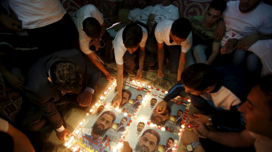 Palestinians light candles on posters depicting Palestinian detainee Mohammed Allan during a protest in support of Allan in the West Bank city of Hebron