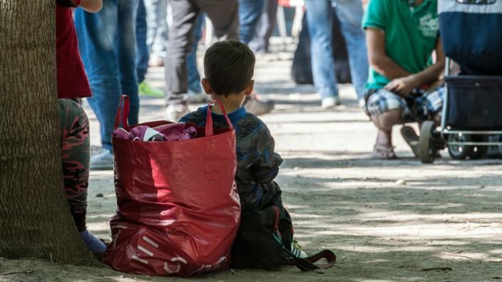 Ein Kind sitzt in Berlin vor dem Landesamt für Gesundheit und Soziales.