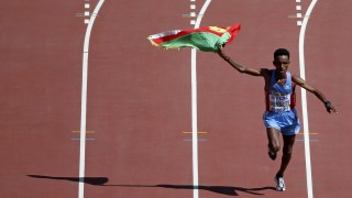 Ghirmay Ghebreslassie of Eritrea celebrates as he enters the stadium to win the men's marathon at the 15th IAAF World Championships at the National Stadium in Beijing