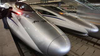 A man looks at the bullet trains serving the new high-speed railway linking Shanghai and Hangzhou in Shanghai