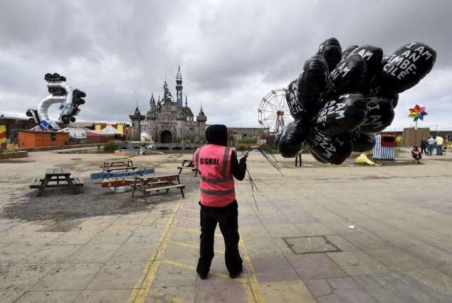 A performer holds a bunch of balloons at 'Dismaland', a theme park-styled art installation by British artist Banksy, at Weston-Super-Mare in southwest England