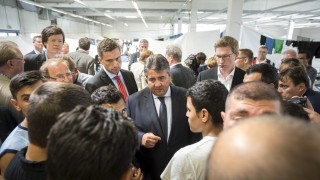 Germany's Vice Chancellor and SPD leader Sigmar Gabriel speaks with migrants from Syria and Afghanistan as he visits an asylum seekers accommodation facility in the eastern German town of Heidenau
