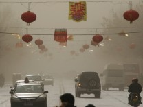 Vehicles move on a street during a sandstorm in Hami