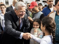 German President Gauck shakes hands with a girl during visit of an asylum seekers accomodation facility in Berlin